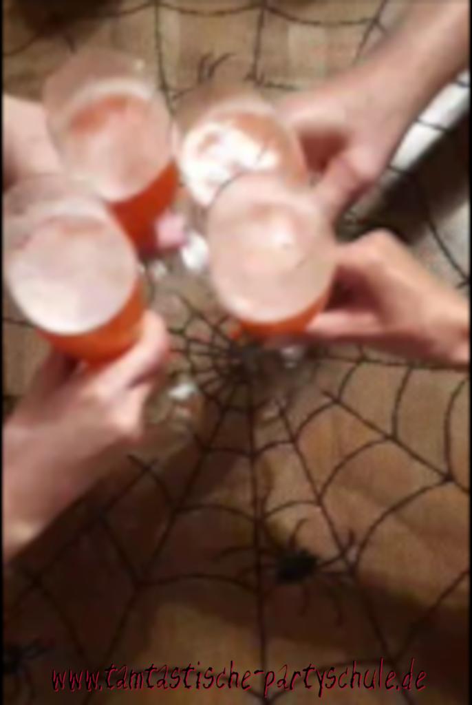 Anstoßen mit rotem Halloween Cocktail