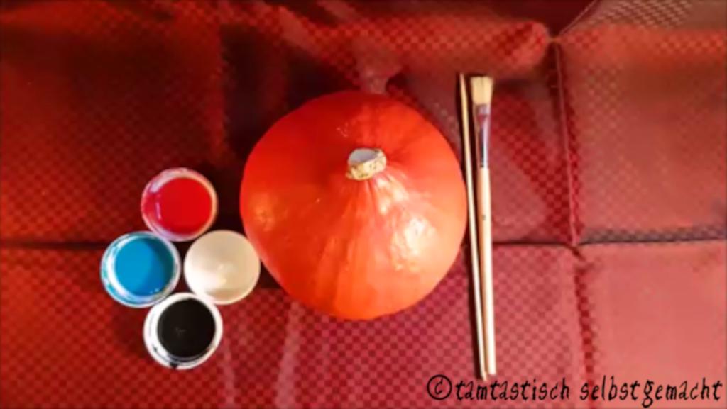 benötigtes Material um einen lachenden Kürbis zu Halloween zu bemalen: Kürbis, schwarze, weiße, blaue & rote Farbe, Pinsel & Schaschlikstäbchen