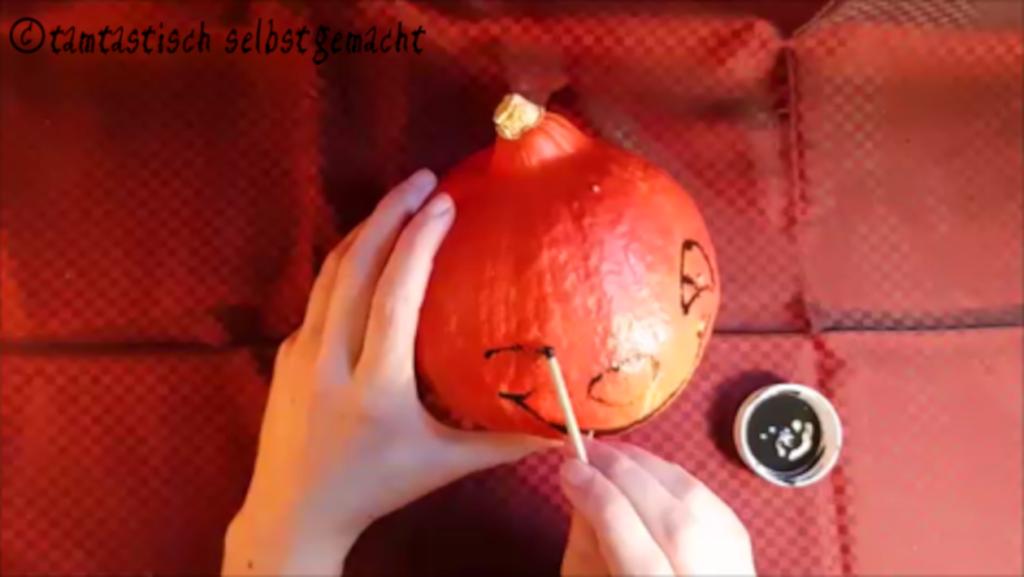 Arbeitsschritte um einen grinsenden Kürbis zu Halloween zu bemalen: Augen malen